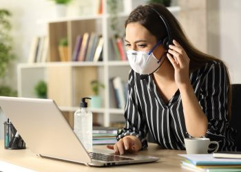Happy telemarketer woman calling on laptop avoiding coronavirus with mask working at homeoffice